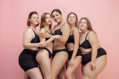 Tapeta Loves herself and feels good. Portrait of beautiful young women with different shapes posing on pink background. Happy female models. Concept of body positive, beauty, fashion, style, feminism