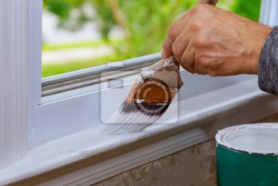 Tapeta Malowanie drewnianym pędzlem podczas malowania tapicerki okna