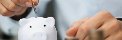 Tapeta Man hand putting coin into white piggy bank closeup