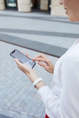 Tapeta Mid section closeup of young businesswoman holding smartphone outdoors in urban area, copy space