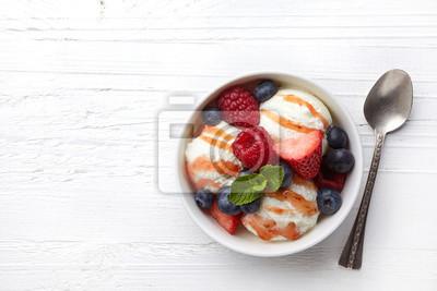 Miska lodów waniliowych z sosem truskawkowym i świeżymi jagodami