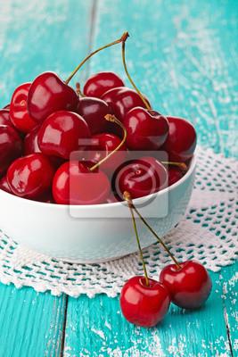 Miska świeżych czerwonych wiśni na niebieskim tle drewniane