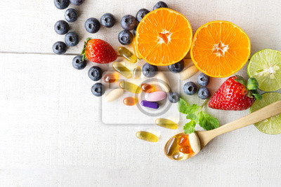 Tapeta Multivitamins and supplements with fresh and healthy fruits on white wooden background.
