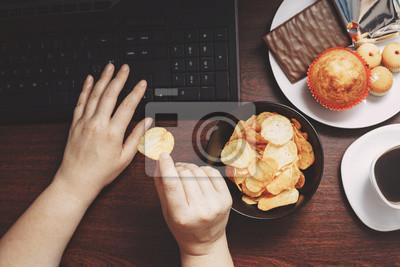 Tapeta Niezdrowe przekąski w miejscu pracy. Ręki pracuje przy komputerem i bierze układ scalony od pucharu kobieta. Złe nawyki, niezdrowe jedzenie, jedzenie wysokokaloryczne, przyrost masy ciała i koncepcja