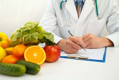 Tapeta Nutritionist doctor writing diet plan on table. Right nutrition and slimming concept