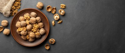 Tapeta Nuts. Walnut kernels and whole walnuts on dark stone table. Black background. Top view, flat lay with copy space.