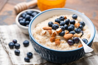 Tapeta Oatmeal with blueberries and almonds in blue ceramic bowl on a wooden table. Closeup view of healthy breakfast food, vegan vegetarian meal
