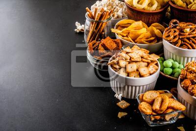Tapeta Odmiana różne niezdrowe przekąski krakersy, słodko solone popcorn, tortille, orzechy, słomki, bretle, tylna tablica kopia przestrzeń