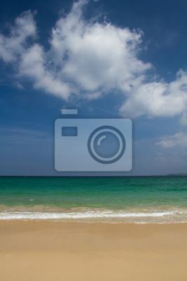 Opuszczona piaszczysta plaża i szmaragdowo zielony ocean pod jasnym błękitnym niebem z białymi, puszystymi chmurami na bezludnej wyspie raju.