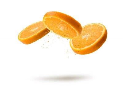 Tapeta Orange fruit slices flying and dripping on white background