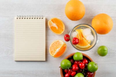 Tapeta Oranges with infused water, green plums, cherries, copybook top view on a wooden background