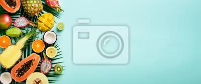 Tapeta Owoce egzotyczne i tropikalne liście palmowe na tle pastelowego turkusu - papaja, mango, ananas, banan, carambola, owoc smoka, kiwi, cytryna, pomarańcza, melon, kokos, wapno. Transparent. Widok z góry