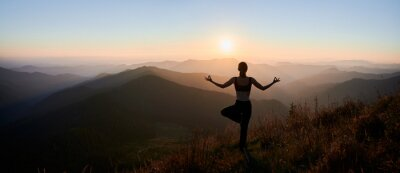 Tapeta Panoramic view of woman practicing yoga on background of evening mountains. Meditating female is balancing on one leg at sunset. Concept of balance.