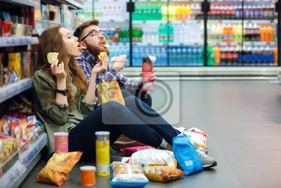 Tapeta Para siedzi na piętrze supermarketu i jedzenia przekąsek