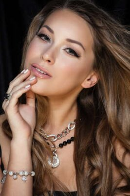 Tapeta Perfect beauty and jewelry concept. Portrait of beautiful female model wearing ring, necklace and wristband on black background. Young blond woman shows glamorous finery.