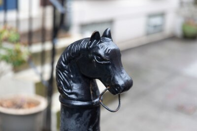 Tapeta Philadelphia, PA - March 26 2021: Metal black horse head hitching post. Historical piece in front of a blurry home in Philadelphia