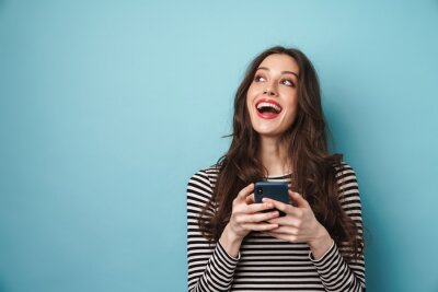 Tapeta Photo of excited nice woman smiling and using cellphone