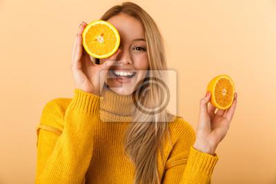 Tapeta Piękna kobieta, obejmujących oczy z cytrusów cytryn pozowanie na białym tle na żółtym tle ściany.