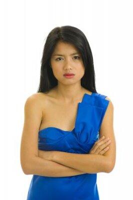 Piękna młoda kobieta azjatyckie z ładnym niebieskim sukienka nie wydaje się być bardzo zadowolony - na białym tle
