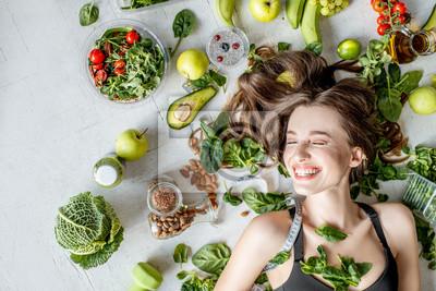 Tapeta Piękno portret kobiety otoczonej przez różne zdrowe jedzenie leżące na podłodze. Koncepcja zdrowego odżywiania i sportowego stylu życia