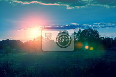 Pole z niebieskim pochmurne niebo o zachodzie słońca. Piękna wieczorna przyroda, krajobraz wiejski, wiosna