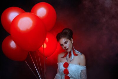 Tapeta portrait cute young woman crazy smiling face clown in white costume stands backdrop dark gothic room holding red balloons evil eyes. art creative bright halloween make-up hairstyle. Fog smoke party