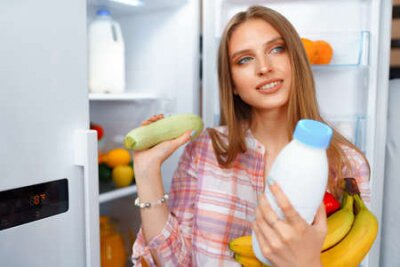 Tapeta Portrait of a young blonde woman taking food from her fridge