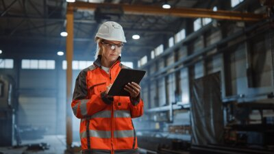 Tapeta Professional Heavy Industry Engineer Worker Wearing Safety Uniform and Hard Hat, Using Tablet Computer. Serious Successful Female Industrial Specialist Walking in a Metal Manufacture Warehouse.