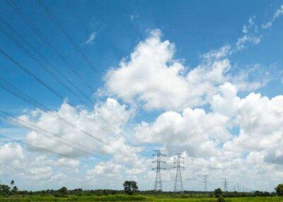 Przekazywanie linii energetycznych i pylon nad polem z ładnym niebieskim i jasnym niebem