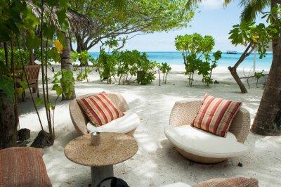Raj na plaży wyspie na Malediwach. Dwa krzesła z poduszkami z luksusowymi zasłonami i stołem dla gości na pierwszym planie. W oddali morzem turkusowym i zielonym palmowym, białym piaskiem. .