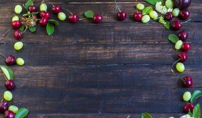 Rama dojrzałe wiśnie z ogrodu z liści, winogron i kwiatów na drewnianej desce. Widok z góry