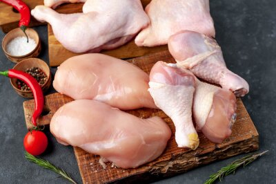 Tapeta raw chicken meat with various parts of fillet, wings, thighs on concrete background