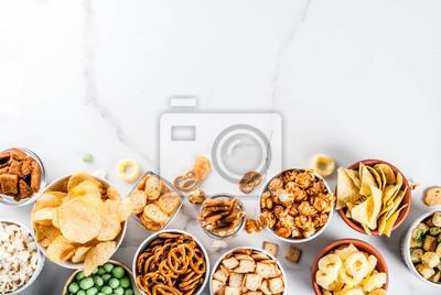 Tapeta Różne różne niezdrowe przekąski krakersy, słodko solone popcorn, tortille, orzechy, słomki, bretle, białe marmurowe tło kopie spaceealthy przekąski