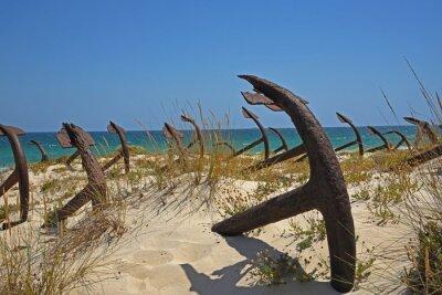 Rusty Metallic Anchors On Sand At Beach Against Clear Sky