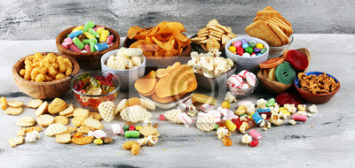 Tapeta Salty snacks. Pretzels, chips, crackers and candy sweets on table