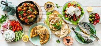 Tapeta Selection of traditional greek food - salad, meze, pie, fish, tzatziki, dolma on wood background, top view