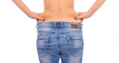 Tapeta Slender girl in big jeans on a white background. Losing weight.