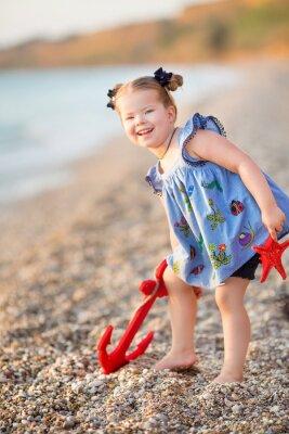 Śliczna mała dziewczynka cieszy się lato czas na dennej strony plaży szczęśliwy bawić się z czerwoną gwiazdą i malutką zabawkarską kotwicą na piasku jest ubranym nobby ubrania z brunetek włosy.