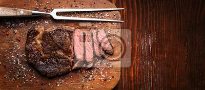 Tapeta smaczny i świeży, bardzo soczysty stek wstążkowy z marmurkowej wołowiny na drewnianym stole.