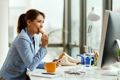 Tapeta Smiling businesswoman eating a cookie while using mobile phone in the office.