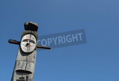 Smiling wooden idol on the background of blue sky. A Jangseung (village guardian) is a Korean totem pole, to scare away demons.