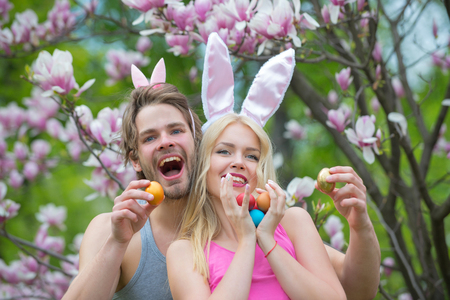 Spring, nature, environment. happy easter of man and woman with eggs. Sensual woman and man with easter eggs. Love and romance, relationship, couple. Couple in love in magnolia flower, spring. family