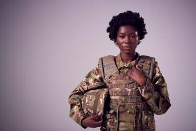 Tapeta Studio Portrait Of Serious Young Female Soldier In Military Uniform Against Plain Background