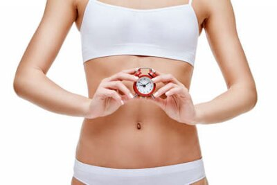 Tapeta studio shot of attractive young woman with beautiful body holding small red alar clock isolated on white