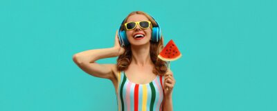 Tapeta Summer colorful portrait of cheerful happy laughing young woman in headphones listening to music with juicy lollipop or ice cream shaped slice of watermelon on blue background