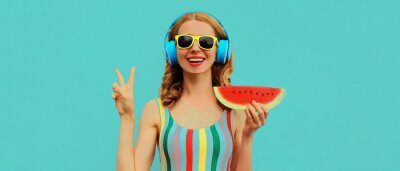 Tapeta Summer colorful portrait of cheerful happy smiling young woman model posing in headphones listening to music with juicy slice of watermelon on a blue background