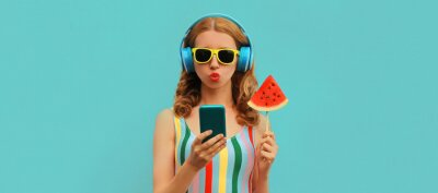 Tapeta Summer colorful portrait of stylish young woman in headphones listening to music on smartphone with juicy lollipop or ice cream shaped slice of watermelon on blue background