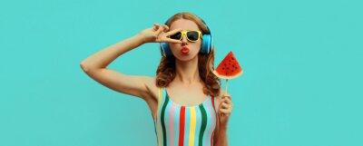 Tapeta Summer colorful portrait of stylish young woman in headphones listening to music with juicy lollipop or ice cream shaped slice of watermelon, model blowing her lips posing on blue background