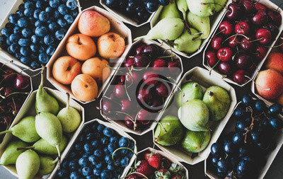 Tapeta Summer fruit and berry variety. Flat-lay of ripe strawberries, cherries, grapes, blueberries, pears, apricots, figs in wooden eco-friendly boxes over grey background, top view. Local farmers produce