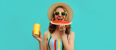Tapeta Summer portrait of happy smiling young woman eating juicy slice of watermelon with cup of juice wearing a straw hat on blue background